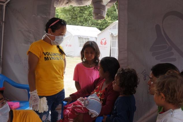 Sous une tente provisoire au Népal, une infirmière - ministre volontaire de Scientologie - envoyé là d'Australie par l'Association internationale des Scientologues (IAS) - écoute la mère d'un bébé d'un mois gravement blessé à la tête