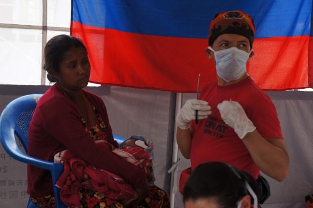 Le responsable de l'équipe du CINAT se prépare à apporter les premiers secours à un enfant blessé